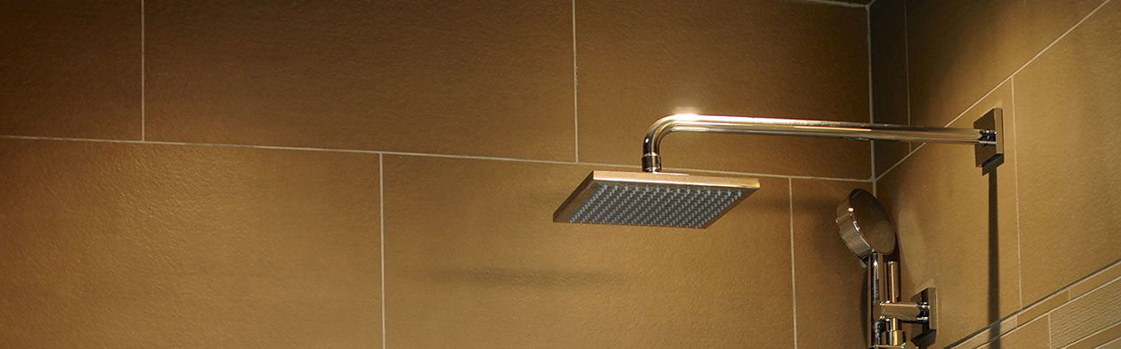 Elegant Shower Head in Renovated Bathroom with Stone Tiled Walls